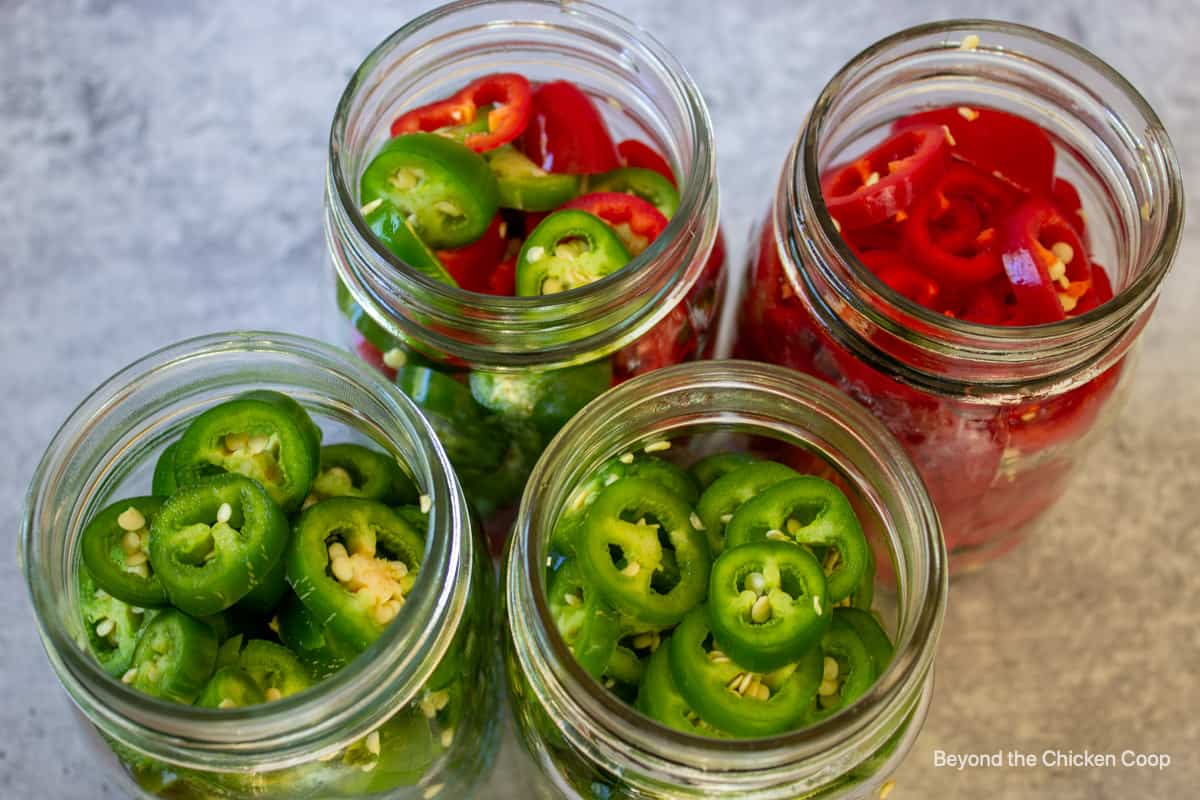 Slice peppers in canning jars.