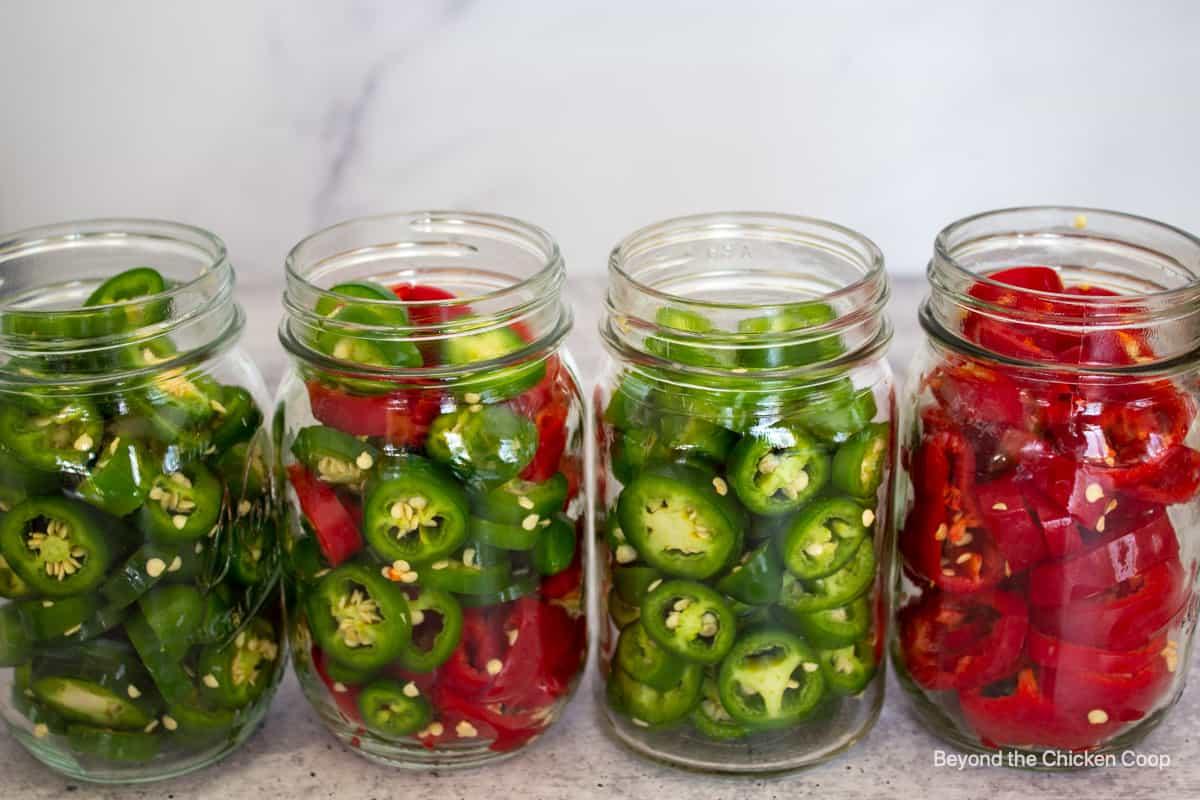 Jars filled with sliced jalapenos.