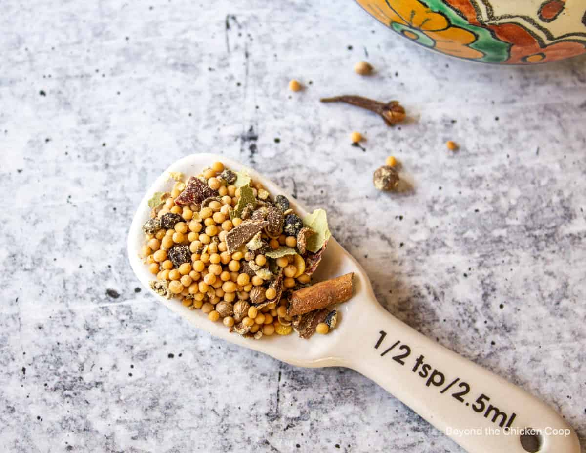 A measuring spoon filled with a mixure of spices.