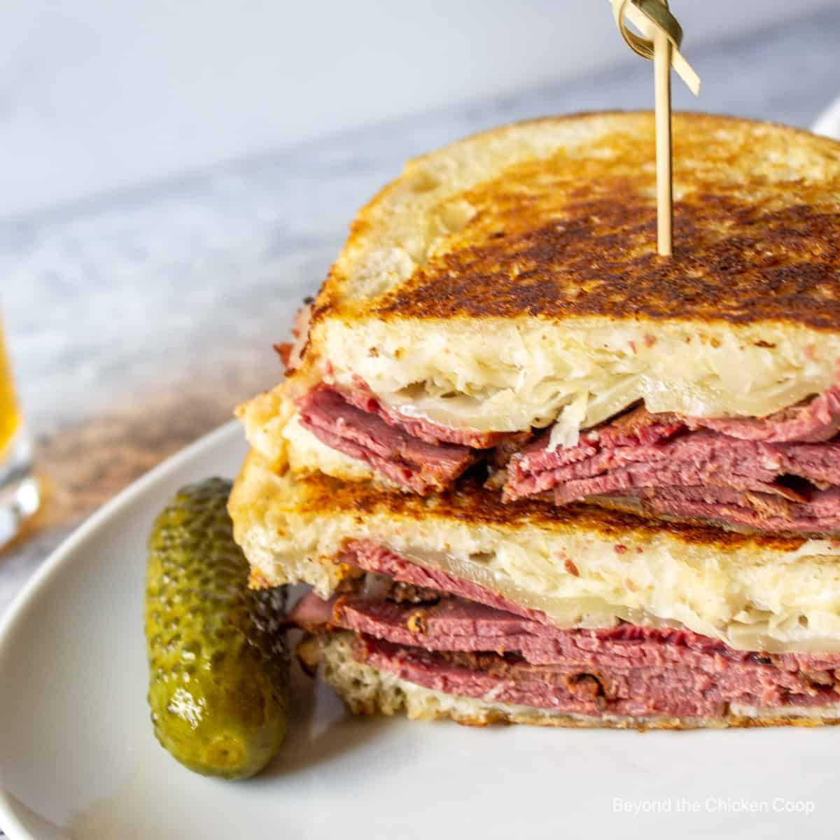 A toasted sandwich with pastrami, sauerkraut and cheese.