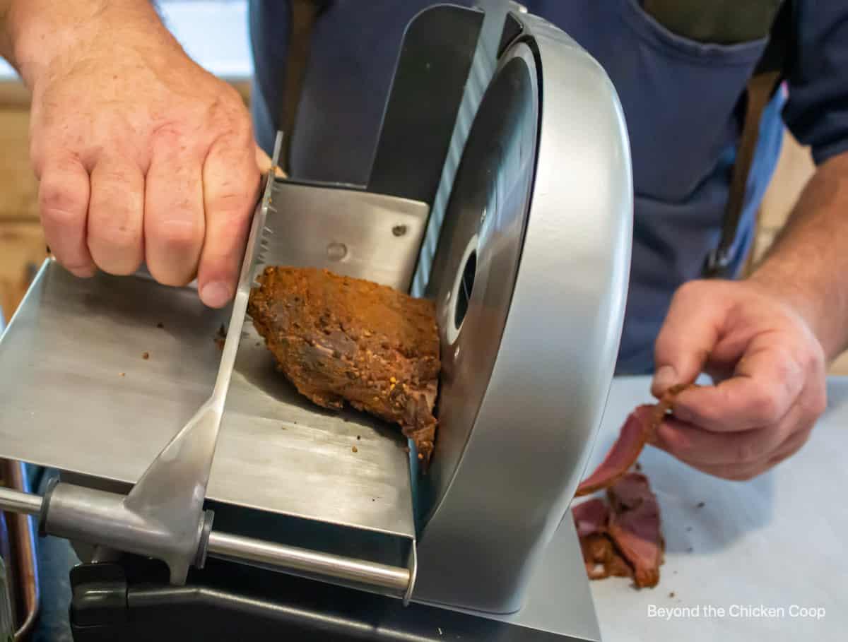 A meat slicer slicing venison pastrami.