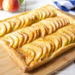 A puff pastry apple tart on a wooden cutting board.