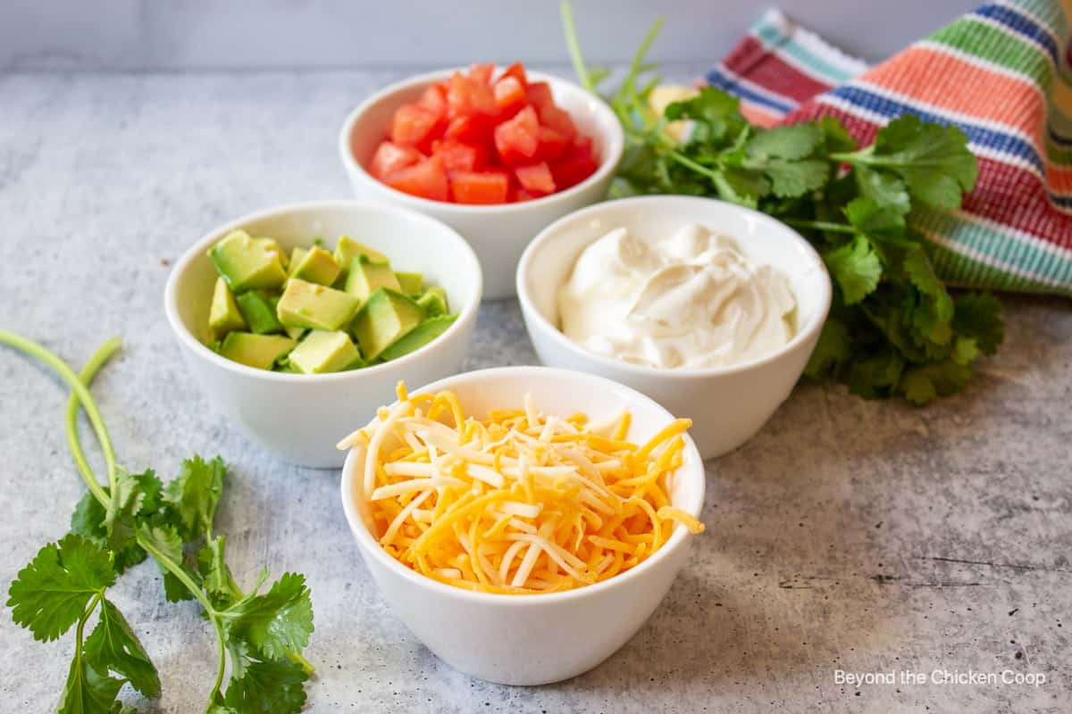 Small bowls filled with cheese, avocado, tomatoes and sour cream.