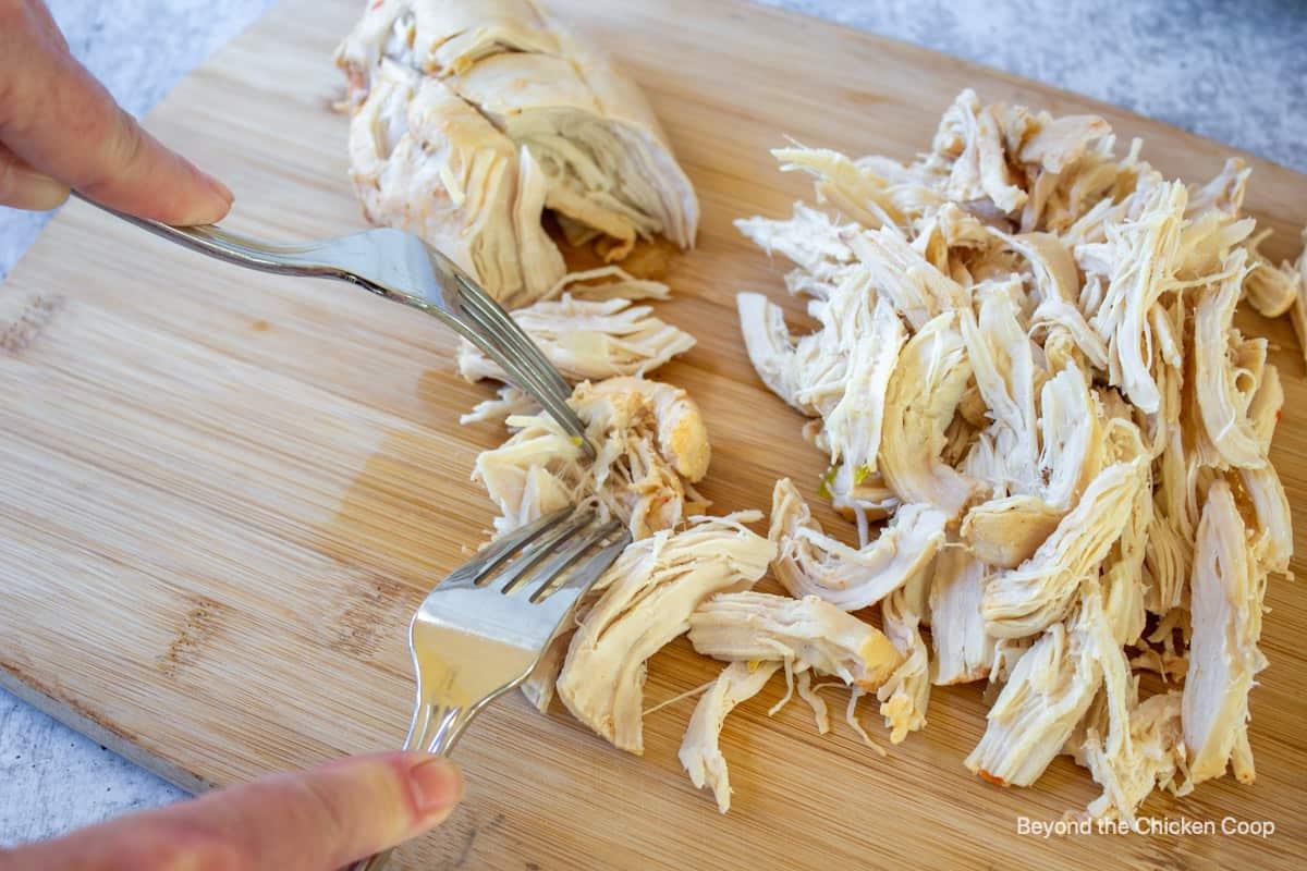 Shredded chicken on a cutting board.