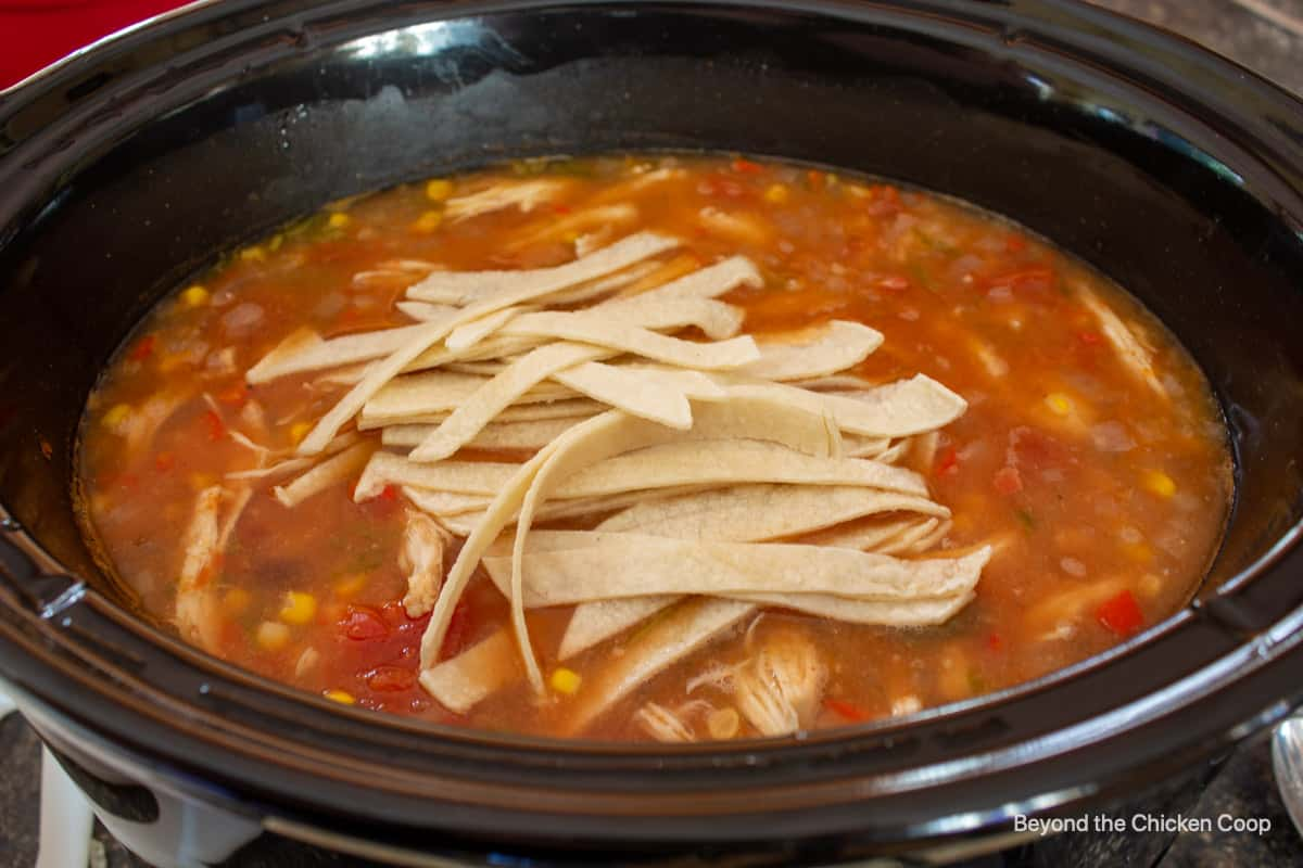 A crockpot filled with chicken tortilla soup.