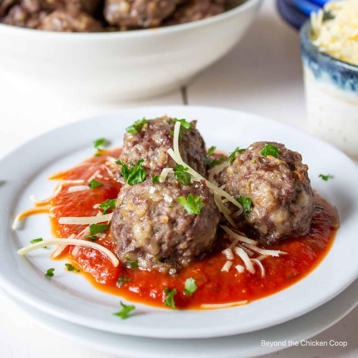 Three meatballs on a plate.